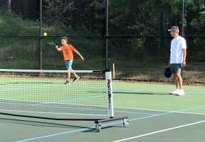 father and son playing pickleball
